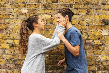 Desperate girl grabs the boy's face with her hands. Wall background composed of brown bricks. External