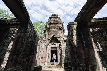 Caucasian blonde woman discovering the ruins of Angkor Wat temple complex in Siem Reap, Cambodia