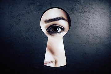 Female eye in keyhole