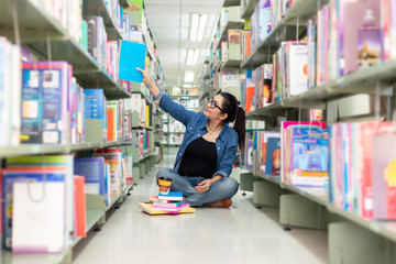 Asian women finding book and reading something in a book,  adult female choosing a book on the bookshelf in a library. Education Concept