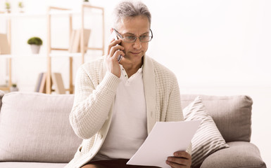 Retired man talking on phone, discussing bills
