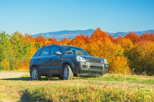 suv on the gravel country road side in mountains. trees in colorful fall foliage on the background. ridge in the distance. travel by car concept