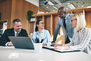 Group of diverse businesspeople laughing together during an offi