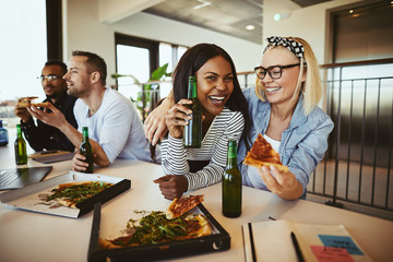 Two businesswomen laughing over pizza and beers after work