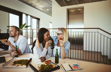 Two laughing businesswomen having beers and pizza after work