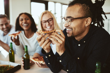 Smiling African American businesswoman having beers and pizza wi