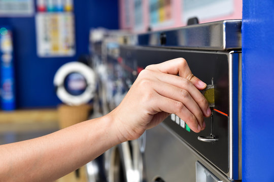 Image of women hand inserting coin into washing machine at self service laundry room