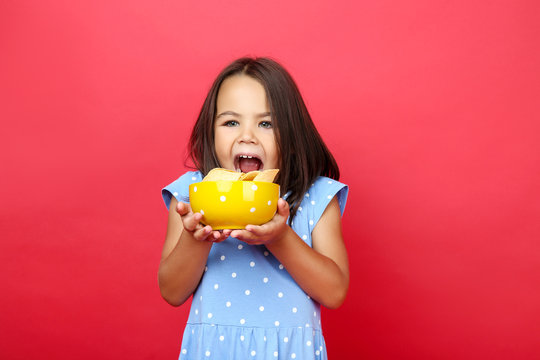 Beautiful little girl with potato chips in bowl on red background
