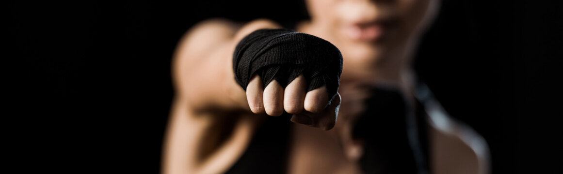 panoramic shot of girl boxing in gloves isolated on black