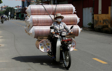 A woman transports paper replica of conical hats to be sold for the Vu Lan Festival, celebrating festival of hungry ghosts by offering daily items for spirits to use in the afterlife, at Dong Ho village, outside Hanoi