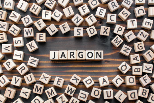 Jargon  - word from wooden blocks with letters,  special words and phrases jargon concept, random letters around, top view on wooden background