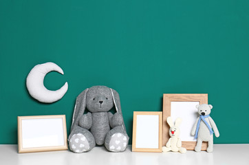 Soft toys and photo frames on table against green background, space for text. Child room interior