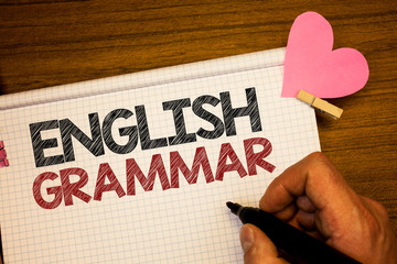 Writing note showing English Grammar. Business photo showcasing Language Knowledge School Education Literature Reading Man holding pen ideas notebook pink heart letters on wooden background