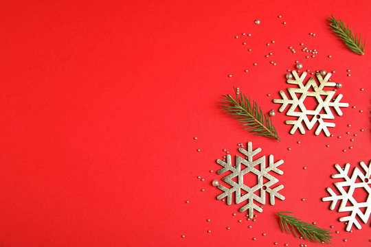 Flat lay composition with Christmas decor on red background. Space for text