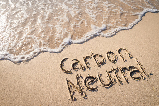 Carbon Neutral message handwritten on smooth sand beach with incoming wave
