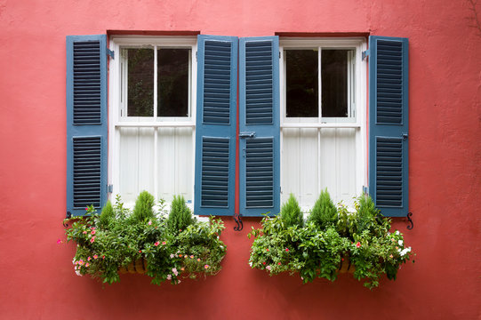 Scenic summer detail of window boxes filled with summer greenery decorating a traditional old Georgian colonial building with blue shutters in Charleston, South Carolina, USA
