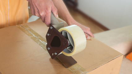 Close up on a woman's hands closing a cardboard box with adhesive tape