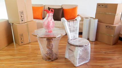 Moving scene with a chair, a vase on a table packed in plastic inside a room with a sofa, plastic rolls and closed cardboard boxes on white background