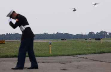 A U.S. Marine holds onto his hat as President Trump approaches in his Marine One helicopter for travel to Pennsylvania aboard Air Force One from Morristown Municipal Airport in Morristown, New Jersey