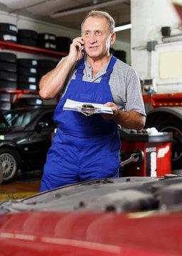 mechanic in auto repair shop making order on phone