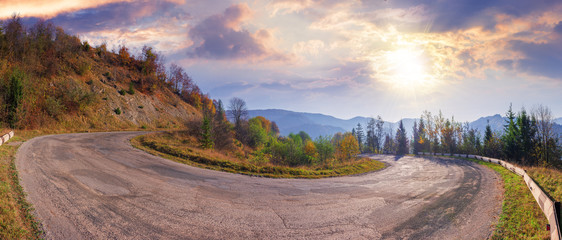 panorama of a serpentine road in mountains.  beautiful autumn scenery in morning light. wonderful september weather with fluffy clouds on the sky. ridge in the distance