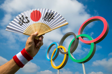 LONDON - APRIL 19, 2019: Hand holding a fan decorated with Japanese kanji characters spelling out hissho (certain victory) at a set of Olympic Rings.