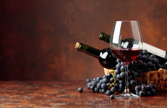 Juicy blue grapes and bottles of red wine on a brown background.