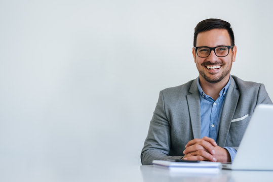 Portrait of young smiling cheerful businessman in office looking at camera copy space