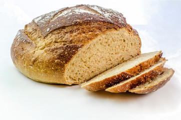 Dark rye bread with three slices on a white isolated background.