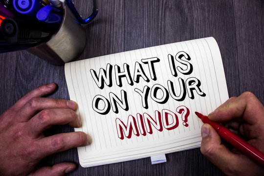 Conceptual hand writing showing What Is On Your Mind Question. Business photo showcasing Open minded thinks of intellectual innovation Man hold holding red marker notebook table messages ideas