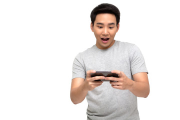 Portrait of an excited Asian man in t-shirt playing games on mobile phone isolated over white background