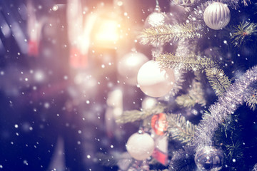 Fototapete - Christmas holiday background. Silver bauble hanging from a decorated on tree with bokeh and snow, copy space.