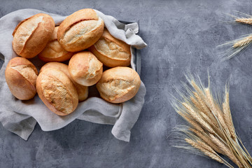 Bread buns in basket on rustic wood with wheat ears, top view on grey