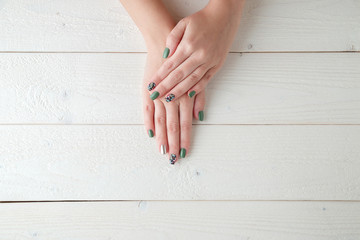 Poster de jardin Manicure women's hands with a beautiful manicure on a light wooden background