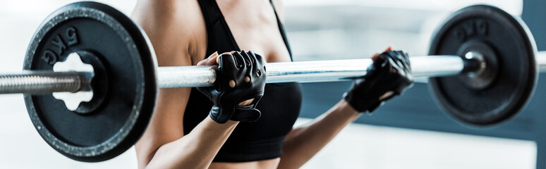 panoramic shot of woman working out with barbell in gym