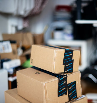 PARIS, FRANCE - DEC 23, 2017: Stack of Amazon Prime cardboard boxes one above another in teenager messy room during Christmas holiday