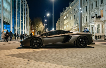 LONDON, UNITED KINGDOM - MAR 9 2017: Rich businessmen party on the balcony with unique luxury super-car parked on Exhibition Rd, Kensington London. Lamborghini Aventador is a mid-engine sports car