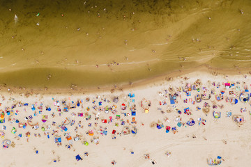 Aerial drone photography of the crowd of people on the beach. Sandy Baltic shore, northern Poland.