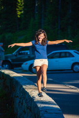 Fototapete - Teenage girl smiling while balancing along a stone wall in Mt. Rainier National Park.