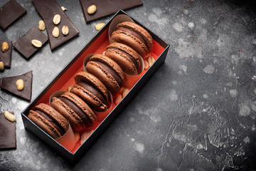 Dark brown chocolate, coffee french macaroons stacked in gift box with pices of chocolate and nuts.