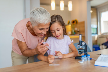 Doing chemical experiment with my grandmother. Child with her granny preparation for scientific experiment. Portrait of happy girl and her grandmother at home.