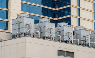 Horizontal image of Six large AC air conditioning HVAC unit on the rooftop of modern hotel business-center skyscraper building
