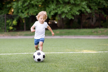 Little football player: blonde child in white shirt and blue shorts running along the green soccer field ready to kick ball. Young sportsman and active childhood concept
