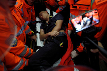 Medics attempt to remove an injured man who anti-government protesters said was a Chinese policeman during a mass demonstration at the Hong Kong international airport, in Hong Kong