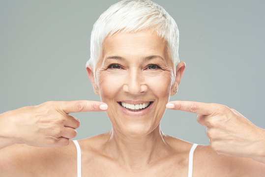 Beautiful Caucasian  smiling senior woman with short grey hair pointing at her teeth and looking at camera. Beauty photography.
