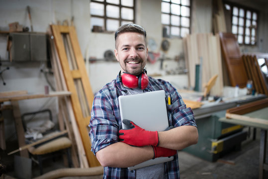 Portrait of experienced architect designer holding laptop computer in workshop.