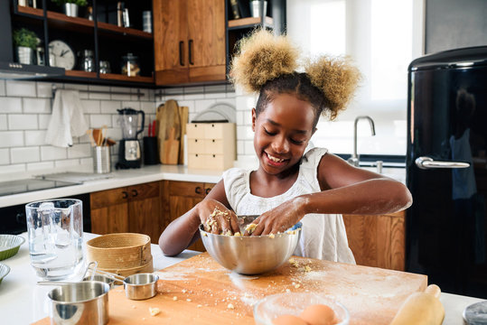 Cute Little African American Girl Making Cookies at Home Kitchen