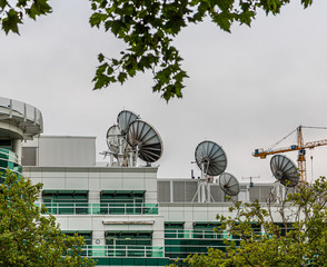 Many Satellite Dishes on Rooftop of a Communicaitons Building
