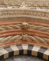 A carved lions head on the entrance to a Siena church