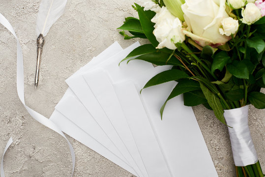 top view of envelopes near bouquet, white ribbon and quill pen on grey textured surface